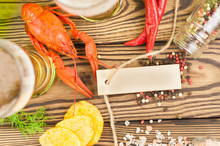 Single Red Boiled Crayfish Near Glasses Of Beer And Fresh Green Dill And Potato Chips And Scattered Pepper And Salt And Red Hot Pepper And Blank Rectangle Paper With Rope On Old Brown Rustic Table