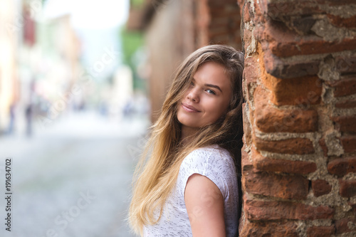 Fotografía Young beautiful girl posing on city street against backdrop of vintage wall, smi