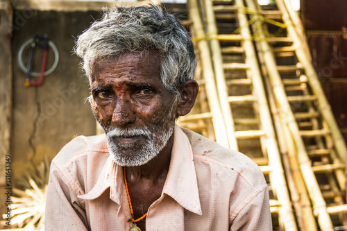 Portrait of Indian elder man with traditional bindi as a third eye, white beard, bamboo ladders on the background and a saw hanging from the wall in Mysore, Karnataka, India Fototapeta