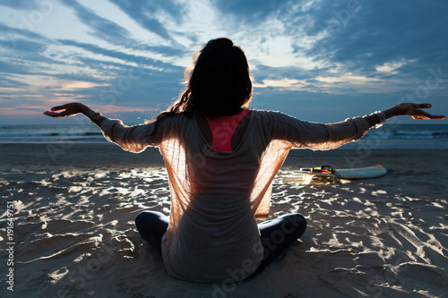 Fotografie, Obraz  Indian surfer girl with long hair sitting on the beach in lotus pose embracing l