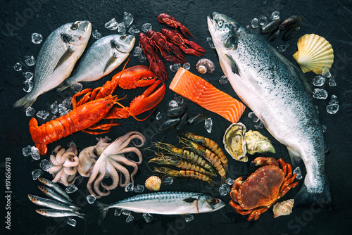 Fotobehang Vis Fresh fish and seafood arrangement on black stone