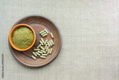 Photo  Supplement kratom green capsules and powder on brown plate