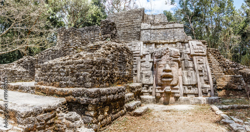 Tuinposter Rudnes Old ancient stone Mayan pre-columbian civilization pyramid with carved face and ornament hidden in the forest, Lamanai archeological site, Orange Walk District, Belize