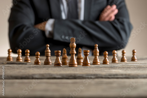 Leinwand Poster Man sitting with folded arms in front of dark chess pieces