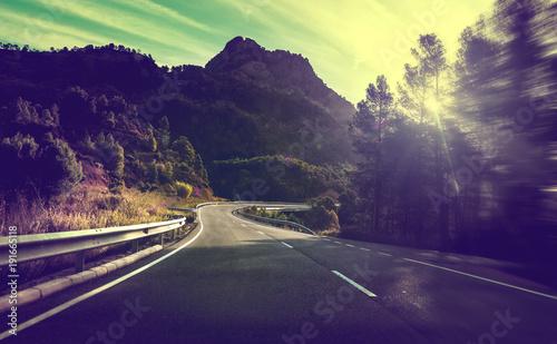 Foto op Canvas Weg in bos Concepto de viajes por carretera.Carretera de montaña con curvas y puesta de sol.Seguridad y precaución conduciendo.