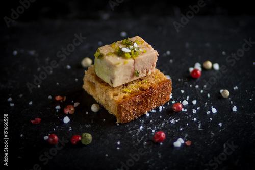 Photo isolated foie gras toast on black plate with sea salt sprinkles