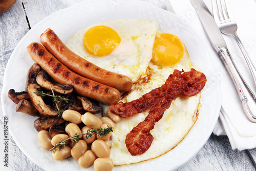 Foto op Plexiglas Gebakken Eieren Traditional full English breakfast with fried eggs, sausages, beans, mushroomsand bacon on wooden background