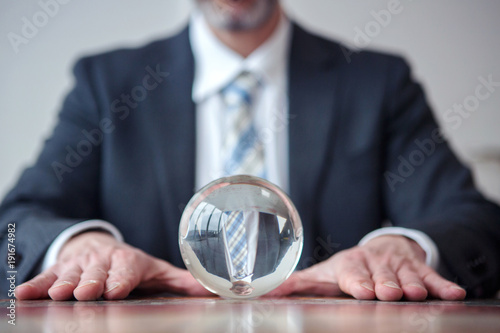 businessman looking at glass ball on table Wallpaper Mural