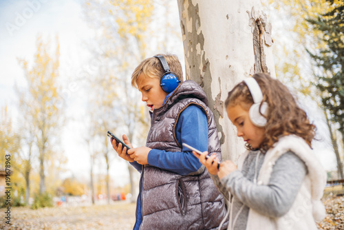 Fotografía  Children listen to music in autumn landscape..
