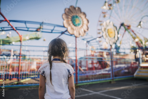 Poster Amusementspark Rear view of girl with pigtails looking at amusement park rides