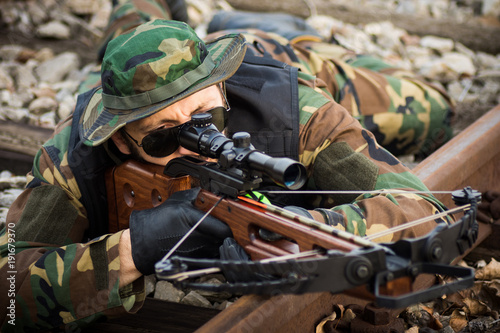 Foto military man aiming with crossbow