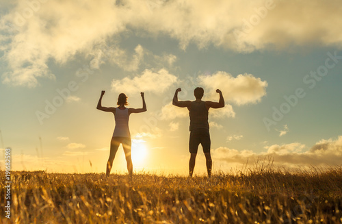 Fotografie, Obraz  Strong man and woman sunset silhouette.