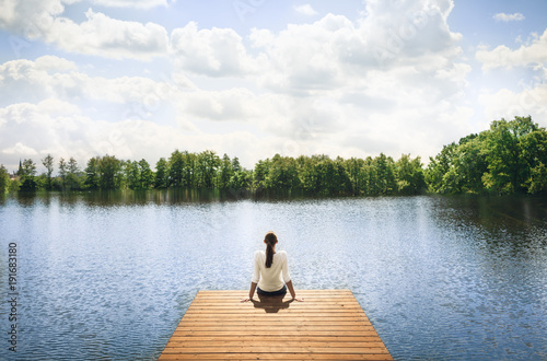 Foto  Woman relaxing on wooden dock by a beautiful lake