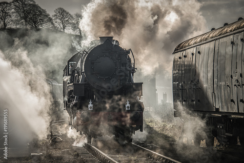 Fotografía A early morning back lit photograph of a steam train smoking and letting off ste