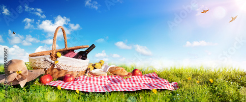 Foto auf Leinwand Picknick Picnic - Basket With Bread And Wine On Meadow