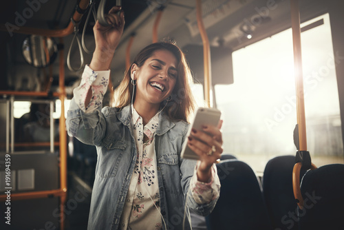 obraz dibond Young woman laughing while listening to music on a bus