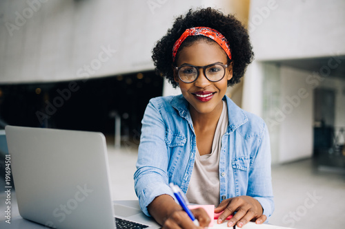 Fotomural  Smiling young African female entrepreneur working on her busines