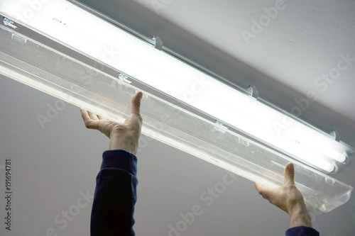 Electric hands changing ceiling fluorescent lamp Wallpaper Mural
