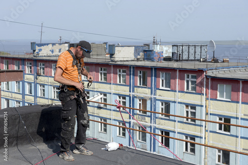 Fotografie, Obraz  steeplejack testing his gear on the roof of the building