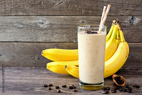 Coffee, banana smoothie in a tall glass with coffee beans and bananas in background. Side view, against a rustic wood background.