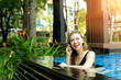 sunshine portrait of happy beautiful woman talking on smart phone swimming at pool. concept of international calls, travel and resting time
