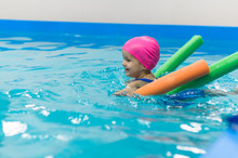 A Little Girl Of European Appearance Floating In The Pool On Inflatable Toy