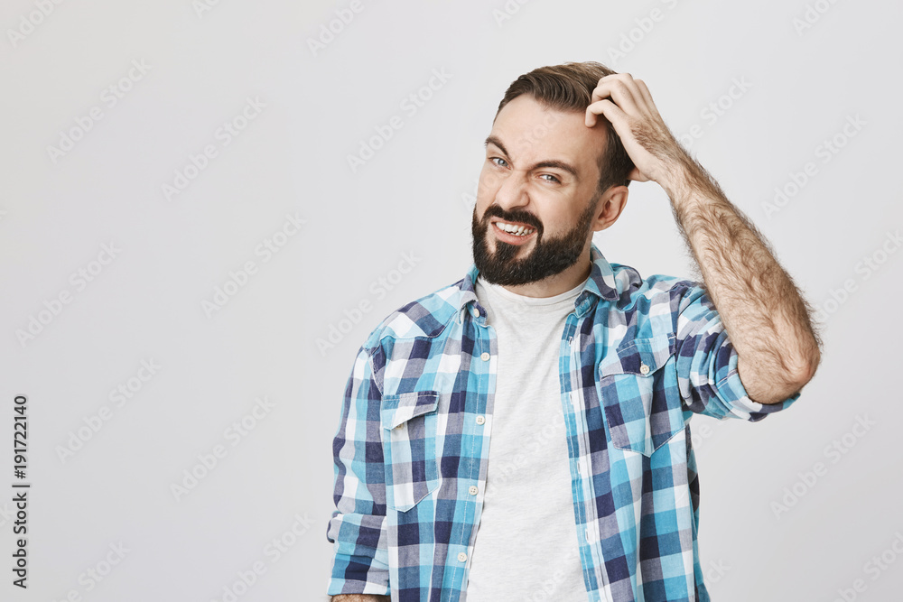 Fototapeta Studio shot of mad bearded male roughly scretching his head and expressing confusion, over gray background. Husband has problems with dandruff, he thinks about buying new shampoo
