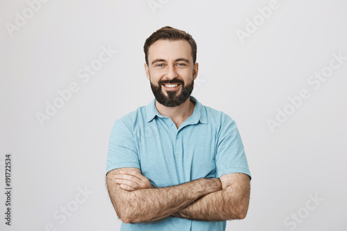 Fotografia  Portrait of a handsome bearded man smiling looking to the camera with his hands crossed isolated on white background
