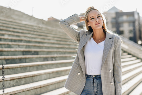 Beautiful young blonde woman in urban background. Tablou Canvas