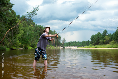 Poster Peche Fishing before the storm. A young man catches a fish on spinning, standing in the river