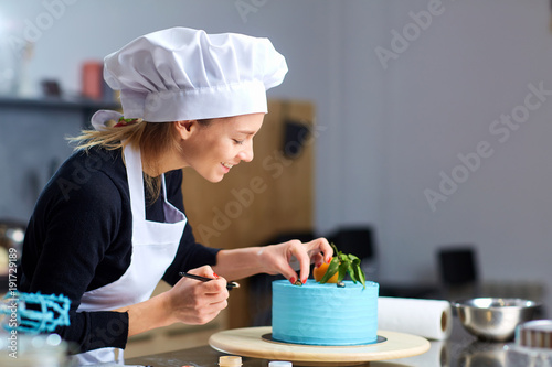 Fotografie, Obraz  A confectioner woman decoration a cake  in kitchen a pastry shop.