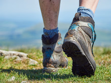 A Close Up Of A Female Hikers Muddy Walking Boots On A Bright Sunny Day