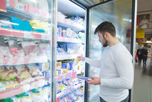 A Man Chooses Frozen Foods Fro...