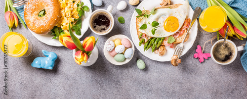 Easter breakfast flat lay with scrambled eggs bagels, orange tulips, bread toast with fried egg and green asparagus, colored quail eggs and spring holidays decorations. Top view. Copy space.