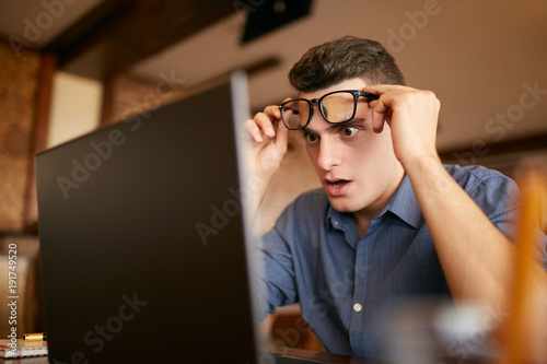 Fotografía  Shocked freelancer hipster man looks to laptop screen and can not believe unpleasant news
