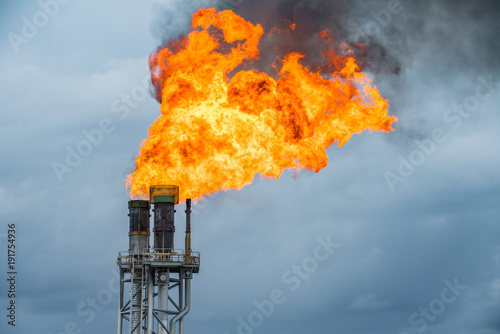Obraz na plátne Fire on flare stack at oil and gas central processing platform while burning toxic and release over pressure from process