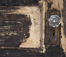 Old Weathered Antique Beat-up Wood Panel Door With Chipped Peeling Paint And Glass Crystal Doorknob And Rusted Plate