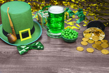 Saint Patrick's Day. Green Hat Of Leprechaun With Green Pint Of Beer, Gold Coins, Smoking Pipe And Green Candies On Wooden Background.