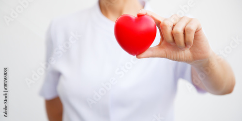 Fotografía  Red heart held by female nurse's hand, representing giving all effort to deliver high quality service mind to patient
