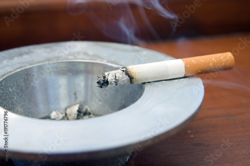 Fotografiet  Burning cigarette smoking on an ashtray