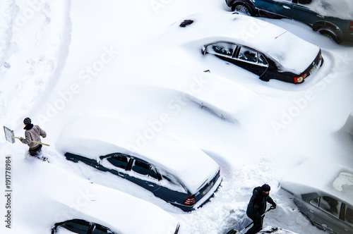 After a snowstorm, people dig out cars from under snow Canvas Print