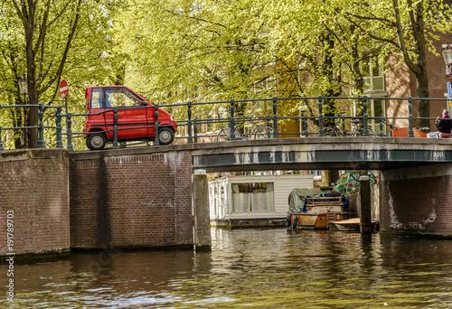 Photo  Mini Car crossing a Bridge in Amsterdam canal, Netherlands