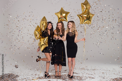 4f48034a6202 Three beautiful girls in black dresses are holding wineglasses with  champagne. Star-shaped balloons