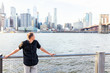 Back of young man outside outdoors in NYC New York City Brooklyn Bridge Park by east river, railing, looking at view of cityscape skyline