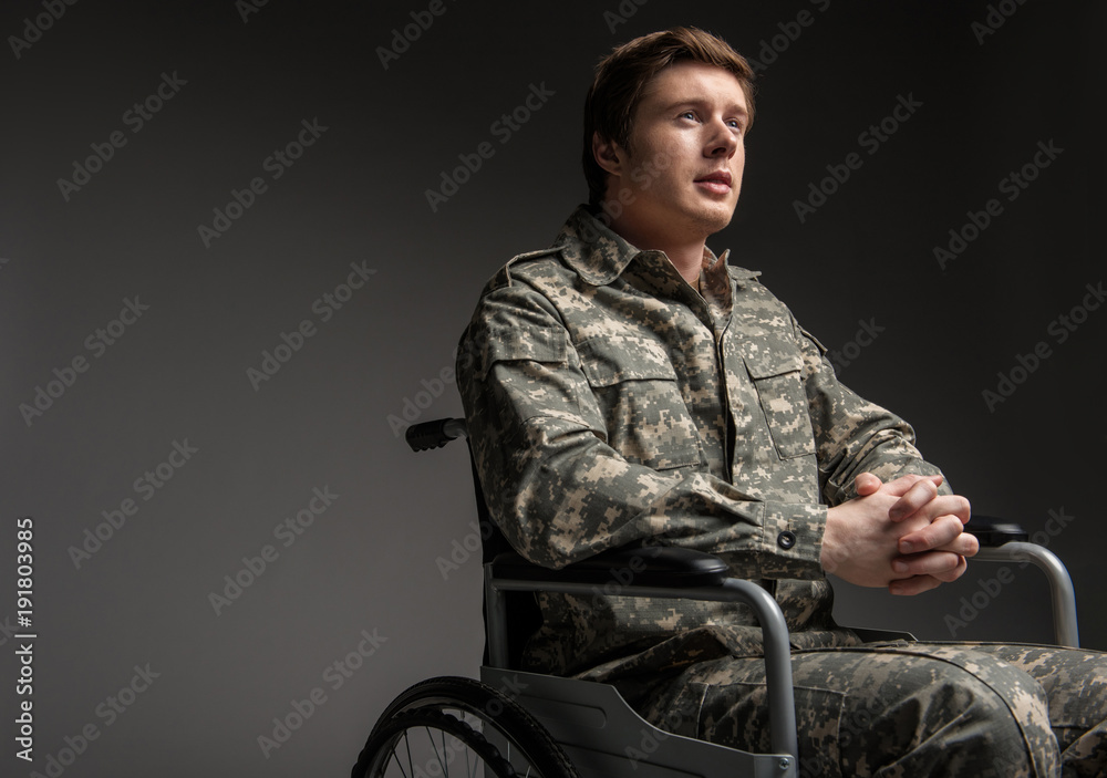 Fototapety, obrazy: Cheerful disabled young military man looking up with hope. He is sitting in wheelchair with his hands folded in the lock. Isolated on grey background. Copy space in left side