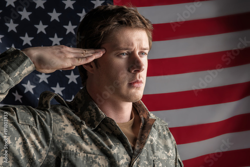 Fototapeta Portrait of serious young male officer saluting with hard look