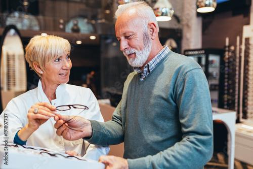 Plakat Przystojny starszy mężczyzna wybiera eyeglasses obramia w okulistycznym sklepie.