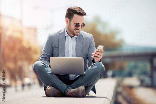 Photo  Young attractive man sitting outside on concrete while using cell phone