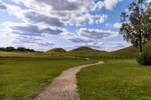 Dirt Path Snakes Its Way Through The Field To The Royal Burial Mounds In Gamla Uppsala, Sweden Under A Blue Sky With Fluffy White Clouds