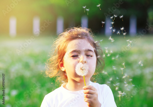Photo sur Aluminium Pissenlit Beautiful little Girl blowing dandelion flower in sunny summer park. Happy cute kid having fun outdoors at sunset.